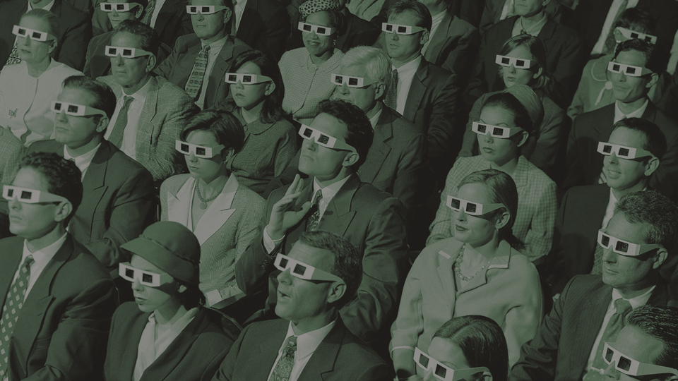 People in a 1950s theatre with glasses